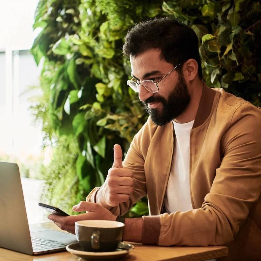 Man thumbs up behind laptop with coffee